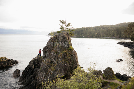 Male backpacker on rock cliff overlooking oceanの写真素材 [FYI02330042]
