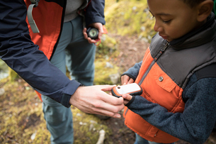Curious boy hiker looking at GPS trackerの写真素材 [FYI02330043]