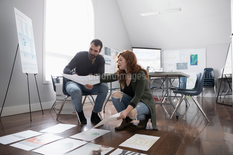 Graphic designers reviewing posters on floor in officeの写真素材 [FYI02330057]