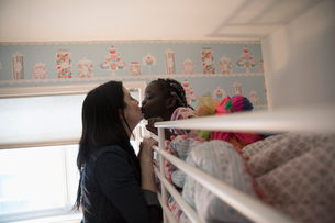 Affectionate mother kissing daughter waking in bunk bedの写真素材 [FYI02330065]
