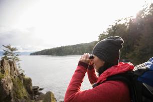 Female backpacker using binoculars, enjoying ocean viewの写真素材 [FYI02330116]