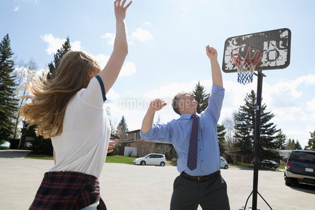 Businessman father playing basketball with tween daughter on sunny streetの写真素材 [FYI02330118]