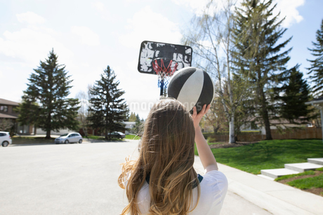 Tween girl playing basketball, shooting the ball on sunny streetの写真素材 [FYI02330151]
