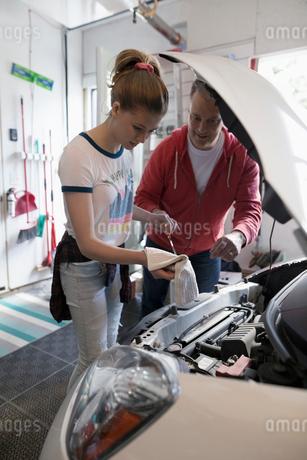 Father teaching tween daughter how to change oil in carの写真素材 [FYI02330194]