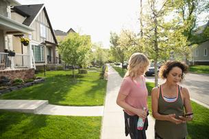 Mature female runner friends using smart phone on sunny neighborhood sidewalkの写真素材 [FYI02330244]