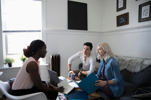 Financial advisor consulting with young couple in living roomの写真素材 [FYI02330333]