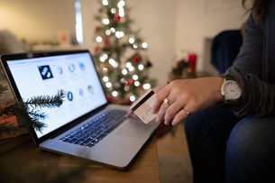 Close up young woman online Christmas shopping at laptopの写真素材 [FYI02330340]