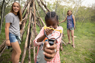 Portrait playful tween girls with slingshot in woodsの写真素材 [FYI02330465]