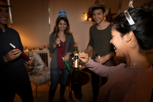 Millennial friends celebrating New Years Eve, opening champagne bottleの写真素材 [FYI02330478]