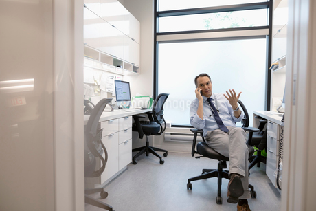 Male doctor talking on smart phone in clinic officeの写真素材 [FYI02330514]