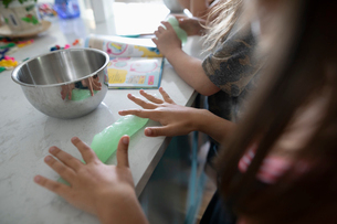 Girl friends making homemade slime in kitchenの写真素材 [FYI02330517]
