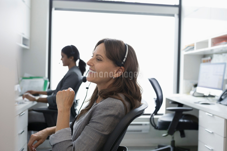Smiling woman using hands-free telephone in clinic officeの写真素材 [FYI02330524]