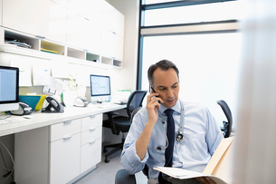 Male doctor talking on smart phone and reviewing medical record in clinic officeの写真素材 [FYI02330527]