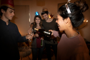 Millennial friends celebrating New Years Eve, pouring champagneの写真素材 [FYI02330554]