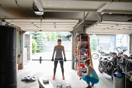 Young women friends working out, weightlifting in garageの写真素材 [FYI02330557]