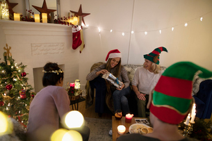 Millennial friends opening Christmas gifts in cozy, candlelit living roomの写真素材 [FYI02330559]
