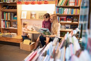 Mother and daughter reading book in bookstoreの写真素材 [FYI02330567]