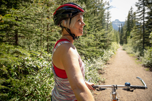 Mature woman mountain biking on sunny forest trailの写真素材 [FYI02330571]