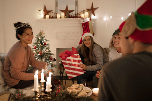 Millennial friends opening Christmas gifts in cozy, candlelit living roomの写真素材 [FYI02330572]