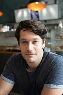 Portrait confident, handsome man in cafeの写真素材 [FYI02330588]