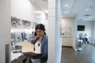 Female doctor with medical record talking on smart phone in clinicの写真素材 [FYI02330593]