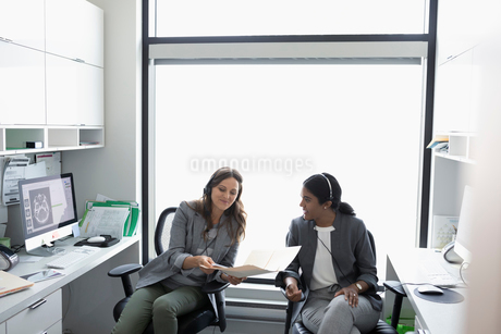 Female doctors discussing medical record in clinic officeの写真素材 [FYI02330597]