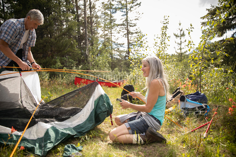 Mature couple setting up tent at sunny forest campsiteの写真素材 [FYI02330606]