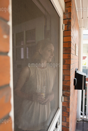 Serene woman standing at porch screenの写真素材 [FYI02330649]