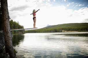 Mature woman on diving board above tranquil lake, Alberta, Canadaの写真素材 [FYI02330653]