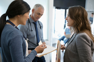 Doctors discussing medical record in clinic corridorの写真素材 [FYI02330675]