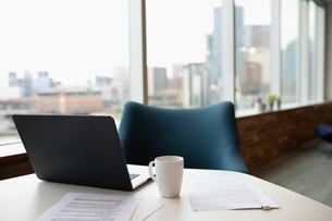 Laptop, paperwork and coffee cup on table in highrise officeの写真素材 [FYI02330678]