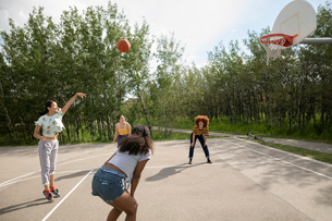 Teenage girl friends playing basketball at park basketball courtの写真素材 [FYI02330685]
