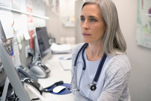 Focused female doctor using computer in clinicの写真素材 [FYI02330699]