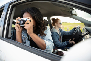 Young woman in car enjoying road trip with friends, using cameraの写真素材 [FYI02330735]