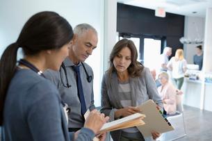 Doctors discussing medical record in clinic corridorの写真素材 [FYI02330744]