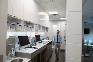 Male doctor walking in clinic corridorの写真素材 [FYI02330780]