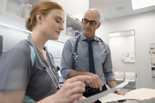 Male doctor and female nurse discussing medical record in clinicの写真素材 [FYI02330821]