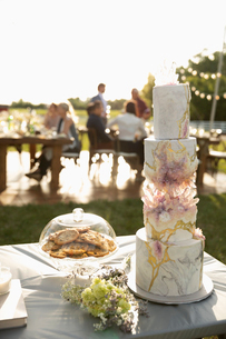 Tiered wedding cake and flowers on patio tableの写真素材 [FYI02330824]