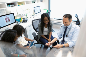 Male doctor with digital tablet talking with mother and daughters in clinic officeの写真素材 [FYI02330857]