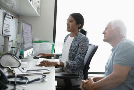 Female doctor and senior male patient at computer in clinic officeの写真素材 [FYI02330863]