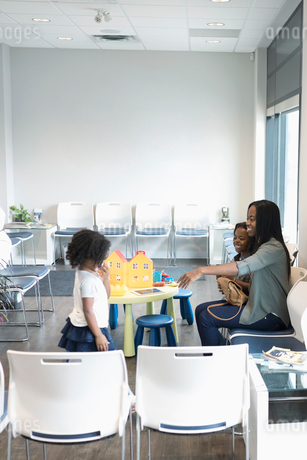Mother and daughters waiting, playing in clinic waiting roomの写真素材 [FYI02330868]