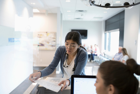 Female doctor discussing paperwork with receptionist at clinic reception deskの写真素材 [FYI02330879]