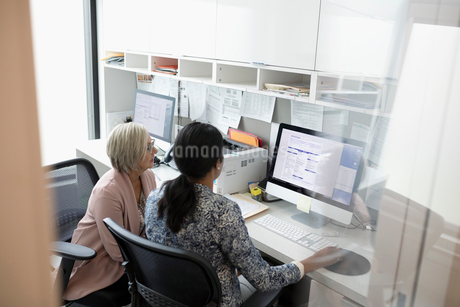 Female doctor and senior patient using computer in clinic officeの写真素材 [FYI02330901]