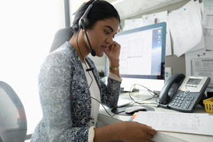 Female doctor with medical record using hands-free telephone at computer in clinic officeの写真素材 [FYI02330923]