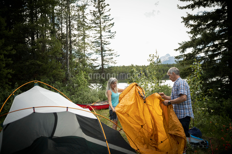 Mature couple setting up tent at lakeside forest campsiteの写真素材 [FYI02330980]