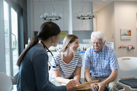 Female doctor talking with senior male patient in clinic waiting roomの写真素材 [FYI02331006]