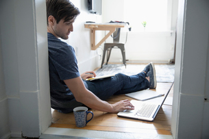 Young man drinking coffee and using laptop on floorの写真素材 [FYI02331049]