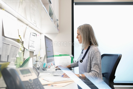 Female doctor working at computer in clinic officeの写真素材 [FYI02331083]