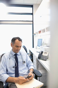 Male doctor texting with smart phone in clinic officeの写真素材 [FYI02331090]