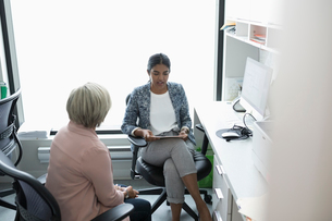 Female doctor discussing medical record with senior patient in clinic officeの写真素材 [FYI02331141]